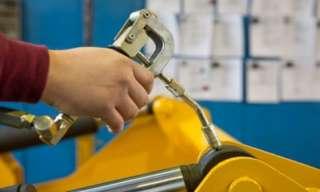 hand eines arbeiters beim abschmieren eines hydraulikzylinders